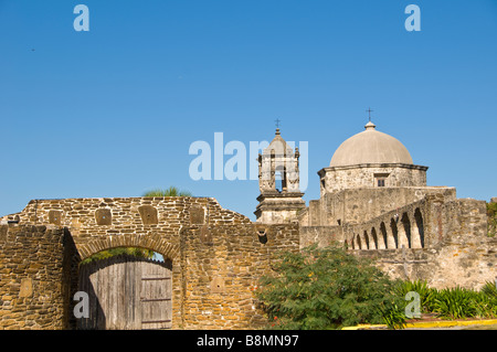 Mission San Jose exterior showing thick stone walls wood entrance door church bell tower and church dome  San Antonio - Stock Image