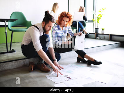 Two business people looking at paper documents on the floor in an office, talking. - Stock Image