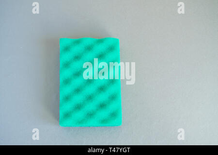 Household cleaning sponge on grey background, top view, flat position, minimalism and cleaning concept, copy of space. - Stock Image