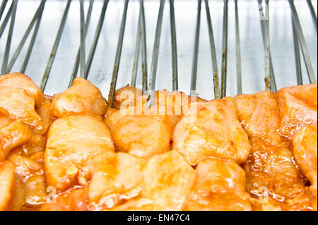 Raw chicken pieces on skewers in a kebab shop - Stock Image