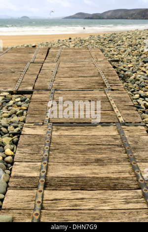 Wooden Walkway over an extensive pebble sea defenses at Newgale beach with sea, cliffs and kitesurfer blurred in distance. - Stock Image