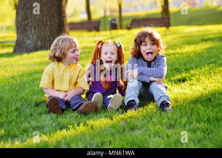 group of happy little children smiling sitting in park on grass under a tree. - Stock Image