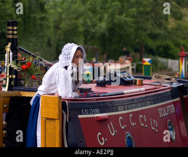 Traditional historic GUCC Ltd narrowboat Sculptor with girl in traditional working cut dress moored at Stoke Bruerne - Stock Image