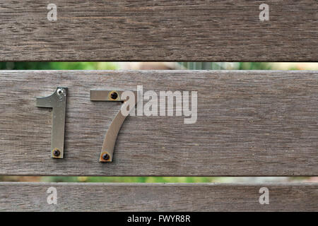 Metal number 17 screwed onto an unpainted wooden fence. - Stock Image