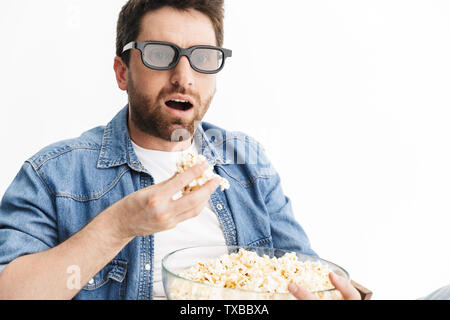 Portrait of a shocked handsome bearded man wearing casual clothes sitting in chair isolated over white background, watching a movie, eating popcorn - Stock Image