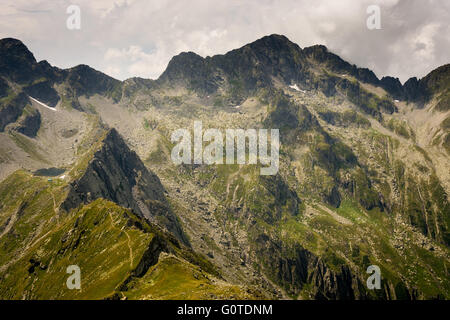 Mountainside with rocky slopes, peaks with cloudy sky in a background and trail from the lake in Carpathian Mountains - Stock Image