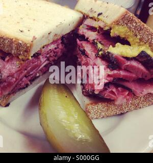 Pastrami and mustard sandwich with pickle, Katz deli, NYC - Stock Image
