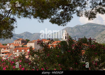 The coastal town of Cavtat in Croatia, framed by trees. - Stock Image