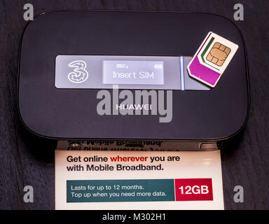 Three data SIM card, holding 12GB of data, which lasts for 12 months, on top of a Huawei portable wifi router, mobile - Stock Image