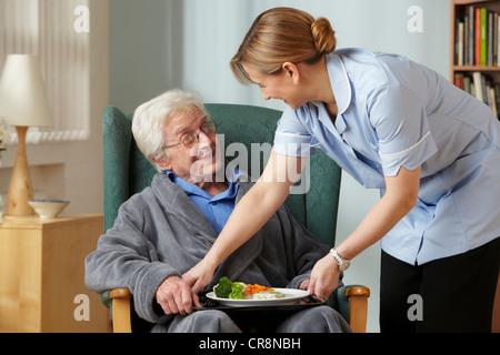 Carer bringing meal to senior man - Stock Image