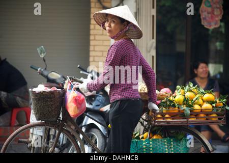 Vietnamese woman trading fruit from her bicycle, Hanoi, Vietnam - Stock Image