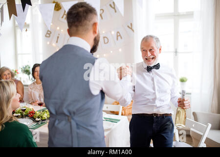 A man giving a bottle of wine to his father on indoor birthday party, a celebration concept. - Stock Image