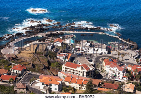 Overhead of town and natural swimming rock pools from Miradouro da Santinha, Madeira, Portugal - Stock Image