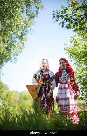 Two young women in traditional russian clothes stand in the field between the trees and singing - vertical shot - Stock Image