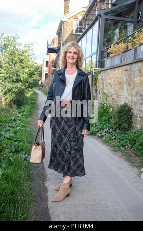 Mature middle aged woman in Autumn fashion clothes by the River Thames at Barnes Mortlake London UK Photograph taken by Simon Dack - Stock Image