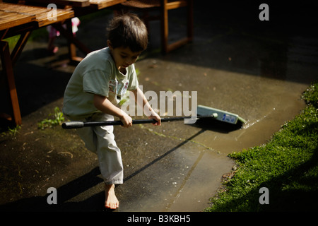 Sweeping away the water Boy aged six with broom - Stock Image