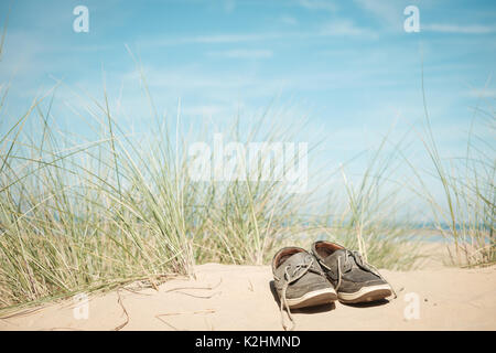man's shoes abandoned on a sand dune on a sunny summer beach in Norfolk, UK - Stock Image