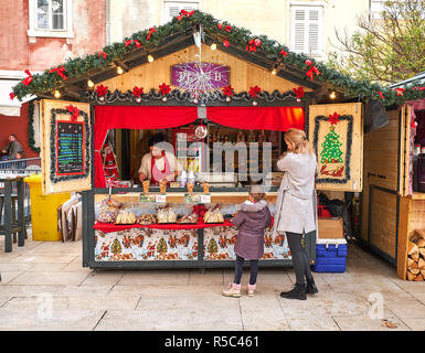 Zadar, Croatia: Fritule (mini donuts) 20 Kuna (local currency) stand at Advent market with mother and kid buying donuts - Stock Image