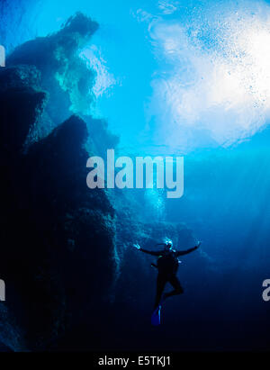 young female diver posing underwater against a steep limestone cliff and a deep blue sea - Stock Image
