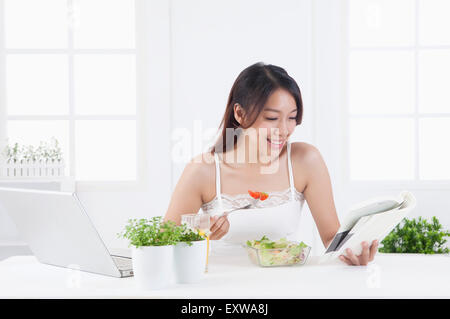 Young woman eating saland and reading a book, - Stock Image