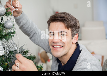 Man With Fairy Lights Decorating Christmas Tree - Stock Image