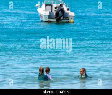 Three children playing in the ocean at Nikki Beach in St Barts - Stock Image