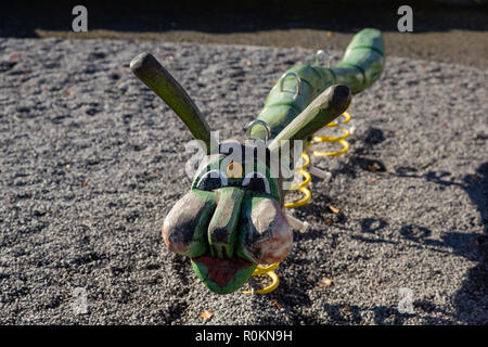 Playground equipment for children to play on - wooden caterpillar on springs. - Stock Image