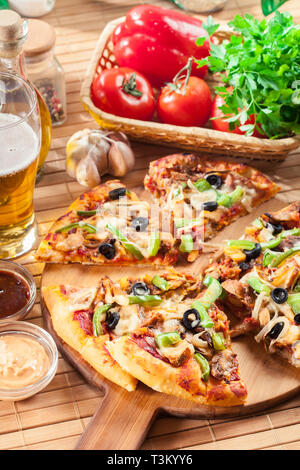 Pizza with chicken gyros, green pepper, olives and onion on cutting board. Served with beer - Stock Image
