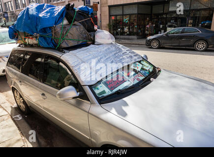 ASHEVILLE, NC, USA-2/3/19: A car has dashboard filled with signs and trash, and filled plastic bags tied on roof. - Stock Image