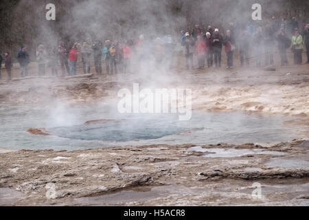 Tourists looking at hot spring after an eruption at Geysir, Iceland - Stock Image