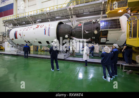 The Russian Soyuz MS-12 spacecraft is encapsulation into the nose fairing of the booster rocket in the Integration Building at the Baikonur Cosmodrome March 6, 2019 in Baikonur, Kazakhstan. The Expedition 59 crew: Nick Hague and Christina Koch of NASA and Alexey Ovchinin of Roscosmos will launch March 14th for a six-and-a-half month mission on the International Space Station. - Stock Image