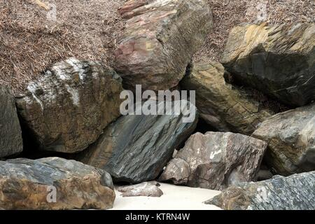 Large rocks piled up on a beach, sand in the foreground. - Stock Image
