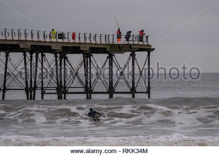 Saltburn-by-the-Sea. 12th Feb 2019. Weather: Dawn on the coast at Saltburn-by-the-Sea on the north-east coast with people fishing from Saltburn Pier and a surfer in the sea. 12th February 2019. © Gary Clarke/Alamy Live News - Stock Image