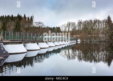 Dam in Lac de Faux during winter in a snow covered landscape near Faux-la-Montagne, Creuse, Nouvelle-Aquitaine, - Stock Image