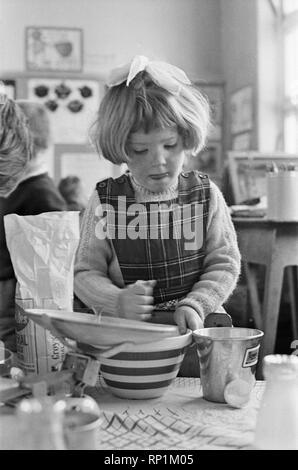 Pancake Making pictures. Five year old pupils from Gawthorpe Infants School, Ussett, West Yorkshire, pictured making pancakes. An experiment thought up by headmistress Margaret Craighan. Picture shows Jane Pickles string her mixture.  Picture taken 4th March 1965 - Stock Image