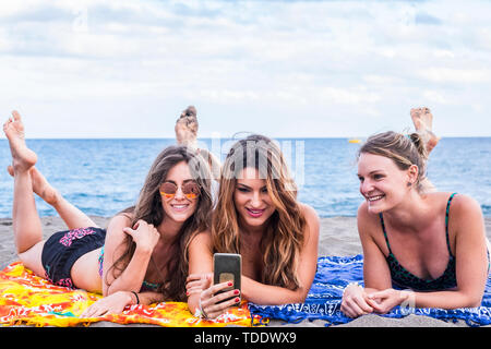 Summer concept with group of three beautiful girls in friendship stay lay down relaxed at the beach speaking and using a smartphone to share her summe - Stock Image