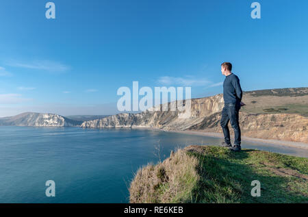 Wareham, UK. Sunday 20th January 2019. A man looks out over Worbarrow Beach on the Jurassic Coast in Dorset. Other people on the beach are wrapped up warm in the 4 degree cold but sunny weather. Credit: Thomas Faull/Alamy Live News - Stock Image