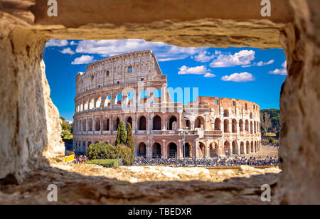 Colosseum of Rome scenic view through stone window, famous landmark of eternal city, capital of Italy - Stock Image