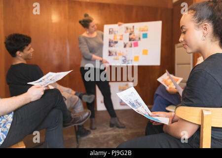 Creative designers brainstorming, reviewing proofs in office meeting - Stock Image
