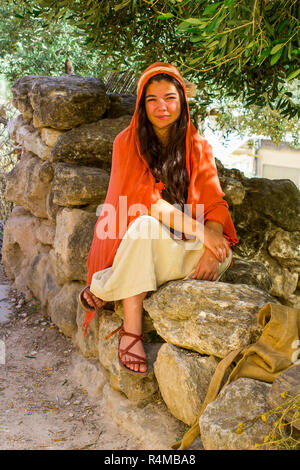 A young woman in period costume in the open air museum of Nazareth Village Israel. This site provides a look at life in ancient Israel - Stock Image