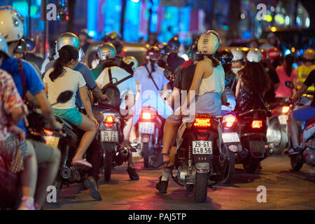 Night shot of mopeds from behind in busy street in Hanoi, Vietnam. The seemingly chaotic traffic scares tourists but is commonplace for locals. - Stock Image