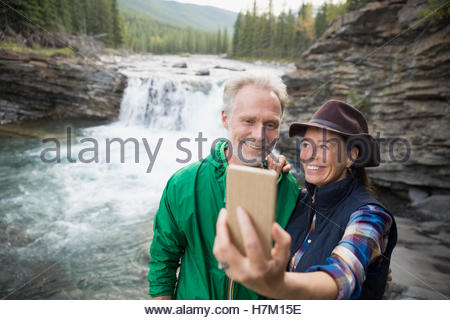 Senior couple taking selfie with camera phone at waterfall - Stock Image