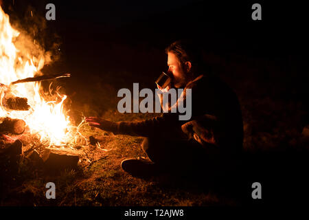 Man drinking by campfire - Stock Image