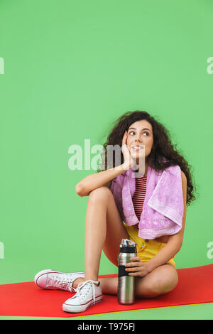 Image of active girl 20s in sportswear with towel over neck resting and sitting on fitness mat after workout against green wall - Stock Image