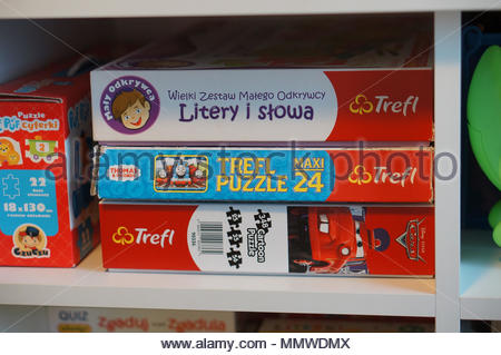 Stacked Polish Trefl puzzles and game in boxes on a wooden shelf - Stock Image