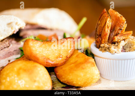 Pub meal with roast potatoes, pork crackling, stuffing and a ciabatta meat sandwich, UK. - Stock Image