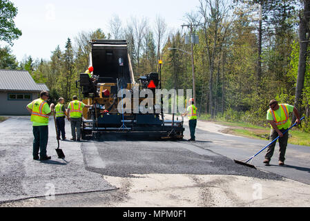 A dump truck and road paver laying asphalt on a parking lot in Speculator, NY USA - Stock Image