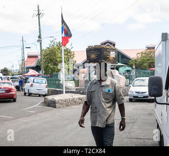 A man carries a box on his head in Saint John's, Capital of Antigua and Barbuda - Stock Image