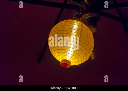 Round silk Chinese or Japanese ribbed globe lantern shade hanging under a patio umbrella glows a bright yellow in - Stock Image