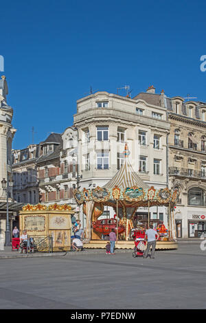 Charming old fashioned traditional carousel children's roundabout in Place de l'Hotel de Ville St Quentin Aisne France - Stock Image